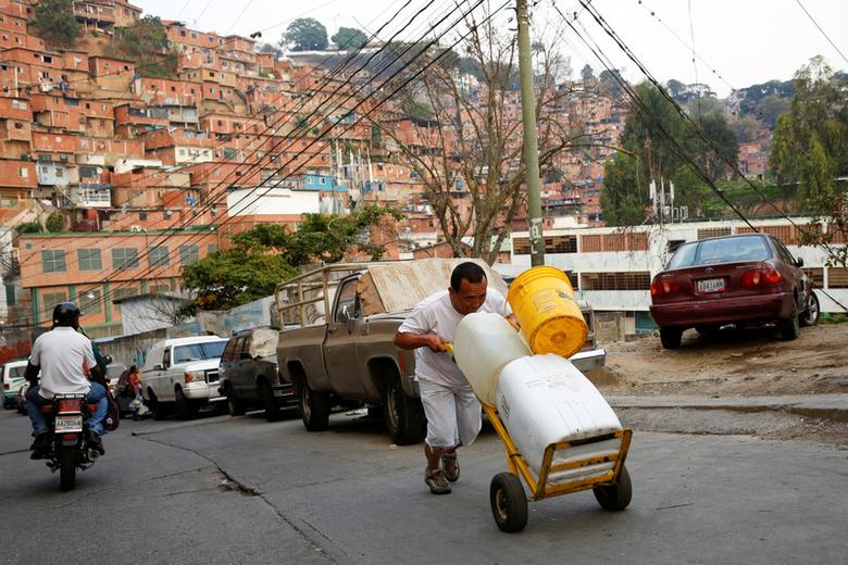 A man pushes a wheelbarrow loaded with water containers in a neighbourhood called ''The Tank'' at the slum of Petare in Caracas, Venezuela, March 17, 2016. REUTERS/Carlos Garcia Rawlins