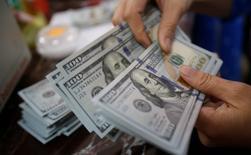 El Ibex-35 de la bolsa española volvía a perder un uno por ciento en la sesión del jueves en un mercado que empieza a descontar una subida de tipos de interés en Estados Unidos incluso a principios de junio tras conocerse las actas de la última reunión del banco central. En la imagen, un empleado bancario cuenta billetes de dólares estadounidense en una sucursal de Hanoi, Vietnam, el 16 de mayo de 2016. REUTERS/Kham