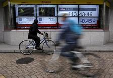 Un hombre en bicicleta mira un tablero electrónico afuera de una correduría en Tokio, Japón. 29 de febrero de 2016. Las bolsas de Asia subían el lunes tras una sesión sólida en Wall Street, y el dólar se alejaba de unos máximos recientes, aunque seguía apoyado por las apuestas de los inversores de que la Reserva Federal de Estados Unidos se encamina a subir las tasas de interés en el corto plazo. REUTERS/Yuya Shino