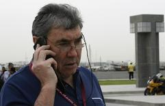 Belgian cycling legend Eddy Merckx talks on his mobile phone while attending the first stage of the Tour of Qatar women's cycling race in Doha January 29, 2013. REUTERS/Mohammed Dabbous