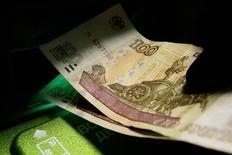 Клиент вносит рублевые купюры в банкомат. Торги на валютном рынке открылись без существенных изменений курса рубля к доллару, на фоне стабильности нефтяных цен и перед вечерней статистикой по рынку труда. REUTERS/Ilya Naymushin