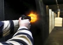 Flames exit the barrel of a gun as a man fires a Sig P320 handgun at the Ringmasters of Utah gun range, in Springville, Utah on December 18, 2015. REUTERS/George Frey - RTX1ZC3J