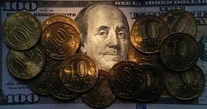 Рублевые монеты на долларовой купюре в Санкт-Петербурге 22 октября 2014 года. Рубль во вторник начал торги небольшим снижением к доллару и евро после комментариев главы ФРС США и на фоне минимальных колебаний нефти. REUTERS/Alexander Demianchuk