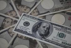 100-долларовая купюра на банкнотах в 10.000 иен. Мрачные настроения на глобальных финансовых рынках заставляют инвесторов, ищущих безопасности, обращаться к традиционно считающимся наиболее надежным валютам - доллару США и японской иене, стимулируя их рост в четверг по отношению к евро, ослабшему из-за перспективы сохранения низкого уровня инфляции и отрицательных процентных ставок. REUTERS/Shohei Miyano (JAPAN - Tags: BUSINESS)