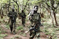 Ugandan soldiers, who are tracking down Lord's Resistance Army (LRA) fugitive leaders, walk at a forest bordering Central African Republic (CAR), South Sudan and Democratic Republic of Congo, near river Chinko April 18, 2012.    REUTERS/Justin Dralaze