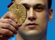 Kazakhstan's Ilya Ilyin poses with his gold medal of the men's 94Kg weightlifting competition at the ExCel venue at the London 2012 Olympic Games August 4, 2012.                                 REUTERS/Dominic Ebenbichler
