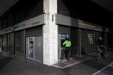 El Banco Central Europeo podría restablecer la próxima semana el acceso de los bancos griegos a las operaciones de financiación barata, dijeron el jueves dos fuentes conocederas de la situación, lo que les permitiría dejar la línea de fondos de emergencia más costosa que usan desde hace más de un año. En la imagen de archivo, una mujer usa un cajero automático en una sucursal de un banco en Atenas. REUTERS/Michalis Karagiannis