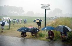 Jun 16, 2016; Oakmont, PA, USA; Spectators seek shelter from the rain during the first round of the U.S. Open golf tournament at Oakmont Country Club. Mandatory Credit: John David Mercer-USA TODAY Sports