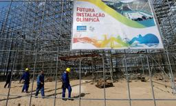 """Workers are pictured at the construction site of the beach volleyball venue for 2016 Rio Olympics on Copacabana beach in Rio de Janeiro, Brazil, June 9, 2016. The sign reads, """"Future Olympic installation"""". REUTERS/Sergio Moraes"""