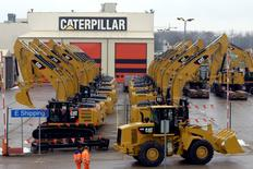 Workers walk past Caterpillar excavator machines at a factory in Gosselies February 28, 2013. REUTERS/Eric Vidal