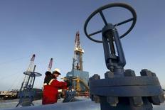 Рабочий проверяет клапан трубопровода на Имилорском нефтяном месторождении. Цены на нефть выросли на азиатских торгах в среду, преодолев отметку $50 за баррель после того, как данные Американского института нефти (API) указали на более сильное, чем ожидалось снижение запасов. REUTERS/Sergei Karpukhin/File Photo