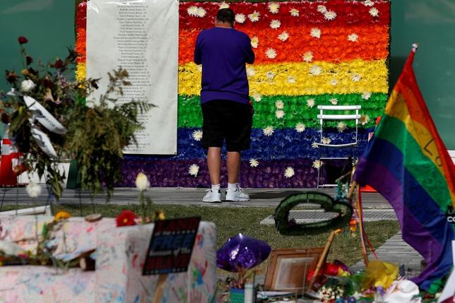 A man pays respect at a rainbow flower wall as part of the makeshift memorial for the Pulse nightclub mass shooting victims last week in Orlando, Florida, U.S., June 21, 2016.  REUTERS/Carlo Allegri