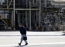Человек проходит мимо завода в промышленной зоне Кэйхин в Кавасаки 17 февраля 2016 года. Производственная активность в Японии снижалась в июне примерно теми же темпами, что и месяцем ранее, согласно предварительным данным, однако опасения, связанные со срывом поставок в результате землетрясения в апреле и падением экспорта, сохраняются. REUTERS/Toru Hanai/File Photo