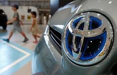 Unos niños caminan cerca de un auto Toyota, en la sala de exhibición de la compañía en Tokio, Japón. 5 de agosto de 2014. La automotriz japonesa Toyota Motor Corp llamó a revisión 3,37 millones de automóviles en todo el mundo por posibles defectos en las bolsas de aires y los equipos de control de emisiones. REUTERS/Yuya Shino/File Photo