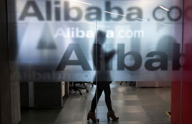 An employee is seen behind a glass wall with the logo of Alibaba at the company's headquarters on the outskirts of Hangzhou, Zhejiang province.  REUTERS/Chance Chan