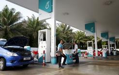 A pump attendant works at a Petronas petrol station outside Kuala Lumpur, Malaysia, March 1, 2016.  REUTERS/Olivia Harris