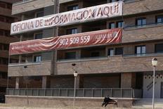 Las ventas de viviendas volvieron a crecer a un ritmo elevado en mayo, en línea con los últimos indicadores que reflejaban una recuperación del sector inmobiliario gracias a la mejora de la economía y el bajo nivel de los tipos de interés. En la imagen, un hombre sentado en un banco junto a un edificio de pisos a la venta en Seseña, Madrid, el 23 de febrero de 2012. REUTERS/Andrea Comas