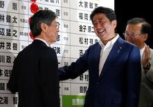 En la imagen, el primer ministro de Japón Shinzo Abe, con un miembro de su partido en la sede de su partido en Tokio, Japón, el 10 de julio de 2016.  El primer ministro japonés, Shinzo Abe, ordenó una nueva ronda de estímulos fiscales después de conseguir una rotunda victoria electoral el fin de semana, mientras el sector corporativo sufre por la débil demanda.  REUTERS/Toru Hanai