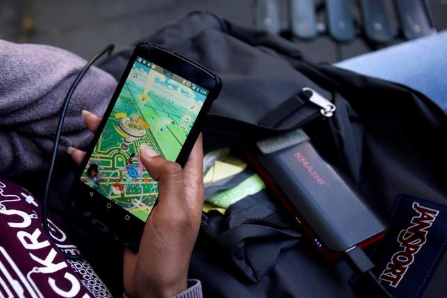 A woman uses a portable battery pack to charge her phone while playing the augmented reality mobile game ''Pokemon Go'' by Nintendo in New York City, U.S. July 11, 2016.  REUTERS/Mark Kauzlarich