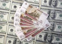 Рублевые и долларовые купюры в Варшаве 9 марта 2015 года.  Рубль вырос в начале торгов четверга на фоне дорожающей нефти и сохраняющегося глобального спроса на риск, благодаря более-менее крупным продажам валюты к налоговому периоду и уплате дивидендов в условиях тонкого летнего рынка. REUTERS/Dado Ruvic