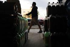 Un hombre camina junto a botellas de bebidas en Ciudad de México. 10 de septiembre de 2013. La mexicana Arca Continental, la segunda mayor embotelladora del sistema Coca-Cola en América Latina, dijo el lunes que su utilidad neta cayó un 9.2 por ciento interanual en el segundo trimestre por mayores gastos financieros y la depreciación del peso que opacaron un fuerte crecimiento en sus ingresos. REUTERS/Edgard Garrido