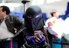 An attendee keeps tabs on her cell phone as she walks the convention floor at the pop culture event Comic-Con International in San Diego, California, United States July 22, 2016.    REUTERS/Mike Blake