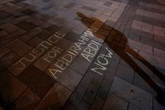 A man casts a shadow near a message written in chalk during a vigil for Abdirahman Abdi, a Somali immigrant to Canada who died after being hospitalized in critical condition following his arrest by Canadian police, in Ottawa, Ontario, Canada, July 26, 2016. REUTERS/Chris Wattie