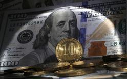 Рублевые мнеты на фоне 100-долларовой купюры. Рубль дешевеет утром пятницы в условиях низких нефтяных цен, обновляющих трехмесячные минимумы, а также после завершения налогового периода, сдерживать рыночную активность могут ожидания совета директоров ЦБР, который, как предполагается, сохранит текущий уровень ключевой ставки 10,50 процента. REUTERS/Alexander Demianchuk