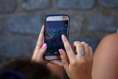 "A young woman plays the augmented reality mobile game ""Pokemon Go"" by Nintendo at Puerta del Sol square in Madrid, Spain July 28, 2016. REUTERS/Sergio Perez"