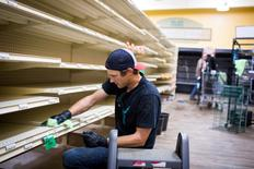 A crew member cleans the inside of a grocery store after clearing all the expired food off the shelves as thousands of evacuees who fled a massive wildfire begin to trickle back to their homes in Fort McMurray, Alberta, Canada June 2, 2016. REUTERS/Topher Seguin