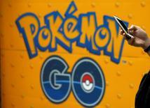 Las grandes compañías de videojuegos, sorprendidas por el enorme éxito de Pokemon Go, están luchando por hallar una forma de emular a la aplicación de realidad aumentada que se ha convertido en un fenómeno mundial. En la imagen, un hombre utiliza un móvil junto a un cartel con la imagen de Pokemon Go en una tienda de Tokio, el 27 de julio de 2016.   REUTERS/Kim Kyung-Hoon/File Photo