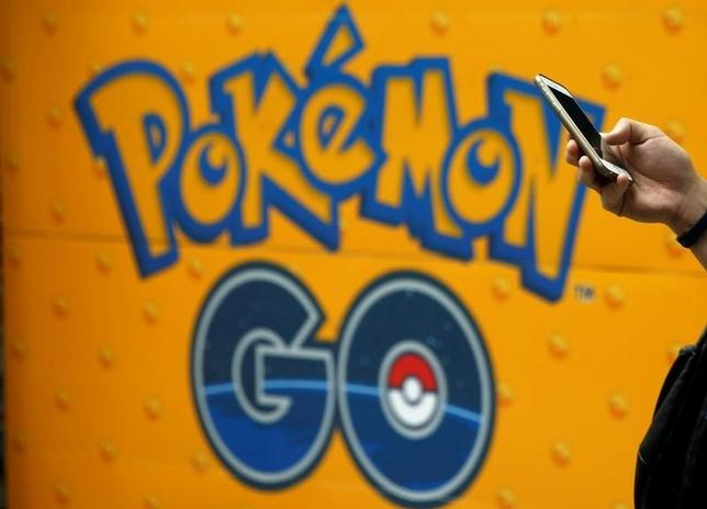 A man uses a mobile phone in front of an advertisement board bearing the image of Pokemon Go at an electronic shop in Tokyo, Japan, July 27, 2016.   REUTERS/Kim Kyung-Hoon/File Photo - RTSLSVC