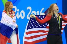 2016 Rio Olympics - Swimming - Victory Ceremony - Women's 100m Breaststroke Victory Ceremony - Olympic Aquatics Stadium - Rio de Janeiro, Brazil - 08/08/2016. Gold medallist Lilly King (USA) of USA and silver medallist Yulia Efimova (RUS) of Russia celebrate with their national flags. REUTERS/Dominic Ebenbichler