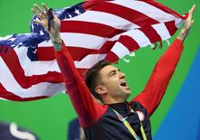 Anthony Ervin of USA celebrates with his gold meda while holding his national flag.      REUTERS/Stefan Wermuth