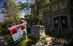 """A """"For Sale"""" sign stands in front of a home that has been sold in Toronto, Canada, June 29, 2015. REUTERS/Mark Blinch - RTX1IBZ1"""