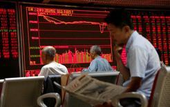 Un hombre lee un diario frente a una pantalla que muestra información bursátil, en una correduría en Pekín, China. 27 de junio de 2016. Las acciones chinas cayeron el miércoles, lastradas por los valores financieros luego de que disminuyeron las expectativas de una relajación de la política monetaria, mientras que los papeles ligados al sector inmobiliario también declinaron. REUTERS/Kim Kyung-Hoon
