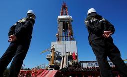 Рабочие смотрят на нефтяную вышку на месторождении Приразломное. Цены на нефть перешли к росту в четверг, оправившись от распродажи в предыдущую сессию, на фоне ожиданий, что доллар ослабнет накануне выступления главы Федеральной резервной системы США Джанет Йеллен в пятницу.  REUTERS/Sergei Karpukhin