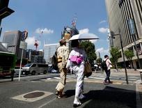 Una pareja camina por un distrito comercial en Tokio. 26 de agosto de 2016. Los precios subyacentes al consumidor de Japón cayeron por quinto mes consecutivo en julio y registraron su mayor declive interanual en más de tres años, luego de que más empresas se abstuvieron de subir los precios debido a la debilidad del consumo. REUTERS/Kim Kyung-Hoon