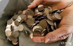 Кассир держит в руках рублевые монеты в Красноярске 22 января 2016 года. Рубль завершает последний торговый день недели ростом к доллару благодаря слабой статистике по рынку труда США, оказавшейся хуже ожиданий, и дополнительной поддержке нефтяных фьючерсов, но давление на российскую валюту в ближайшие дни более вероятно. REUTERS/Ilya Naymushin/File Photo