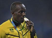 2016 Rio Olympics - Athletics - Victory Ceremony - Men's 4 x 100m Relay Victory Ceremony - Olympic Stadium - Rio de Janeiro, Brazil - 20/08/2016. Usain Bolt (JAM) of Jamaica bites his gold medal. REUTERS/Dylan Martinez