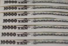 Банкноты 10000 иен. Токио, 28 февраля 2013 года. Иена снизилась повсеместно в среду после сообщения о том, что Банк Японии рассматривает дальнейшие меры смягчения денежно-кредитной политики, в частности возможность ещё сильнее увести ставки на отрицательную территорию. REUTERS/Shohei Miyano/File Photo