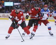 Sep 24, 2016; Toronto, Ontario, Canada; Team Canada forward Sidney Crosby (87)  looks to make a play as forward Patrice Bergeron (37)  holds off Team Russia forward Evgeny Kuznetsov (92) during a semifinal game in the 2016 World Cup of Hockey at Air Canada Centre. Mandatory Credit: John E. Sokolowski-USA TODAY Sports