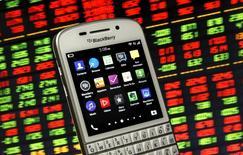 Смартфон Blackberry на фоне дисплея с данными об акциях. BlackBerry Ltd в среду отчиталась об убытке и резком снижении выручки во втором квартале и сообщила, что передаст на внешний подряд производство смартфонов.   REUTERS/Dado Ruvic