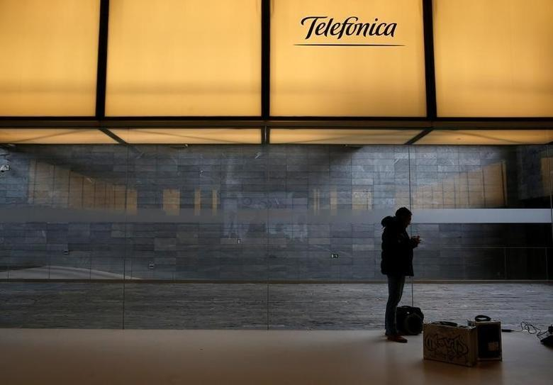 A man stands under a logo of Spain's telecom giant Telefonica at the company's headquarters in Madrid, Spain, February 26, 2016.  REUTERS/Juan Medina/File Photo