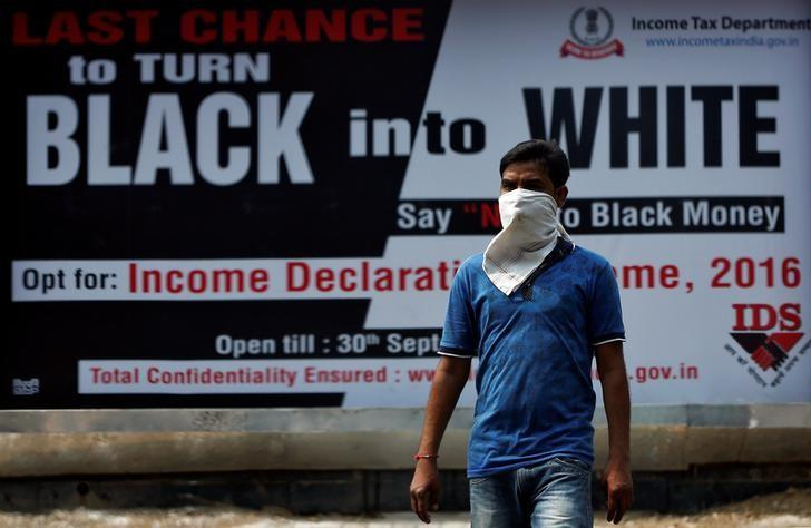 A man walks pasts an income tax billboard in New Delhi, September 26, 2016. REUTERS/Adnan Abidi
