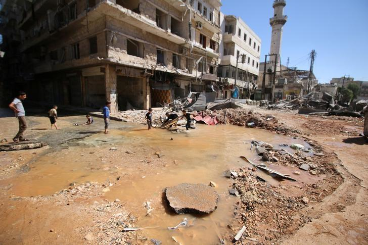 Children play with water from a burst water pipe at a site hit yesterday by an air strike in Aleppo's rebel-controlled al-Mashad neighbourhood, Syria, September 30, 2016. REUTERS/Abdalrhman Ismail