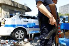 Офицер полиции рядом с поврежденной машиной у входа в здание полиции в Анкаре. Турецкие власти отстранили от работы 12.801 полицейского по подозрению в связях с живущим в США мусульманским проповедником Фетхуллахом Гюленом и его сторонниками, на которых Анкара возложила ответственность за неудавшуюся попытку госпереворота в июле, сообщило главное полицейское управление страны во вторник.  REUTERS/Osman Orsal