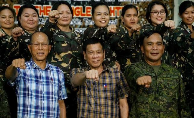 Philippine President Rodrigo Duterte makes a ''fist bump'', his May presidential elections campaign gesture, with defence secretary Delfin Lorenzana (L) and armed forces chief Lt. General Ricardo Visaya (R) and female soldiers during a visit at Capinpin military camp in Tanay, Rizal in the Philippines August 24, 2016. REUTERS/Erik De Castro/Files