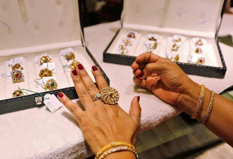A woman tries on a gold ring inside a jewellery showroom on the occasion of Akshaya Tritiya, a major gold buying festival, in Ahmedabad, India, May 9, 2016. REUTERS/Amit Dave