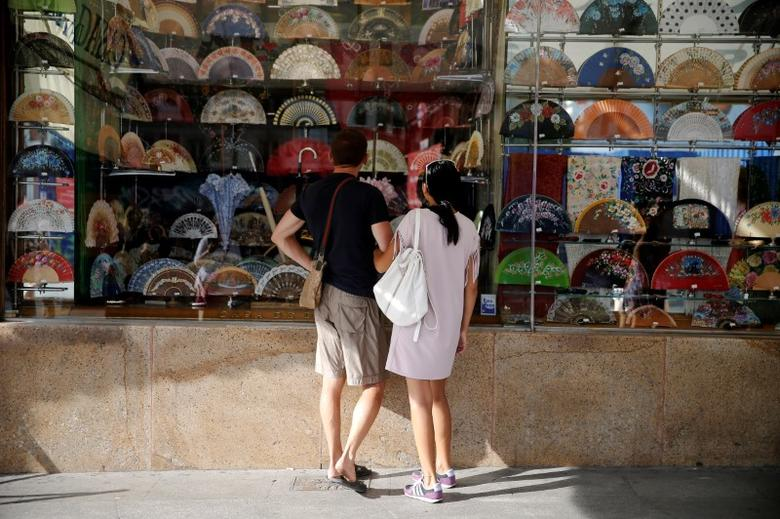 People look at fans inside a shop in central Madrid, Spain August 25, 2016. REUTERS/Andrea Comas